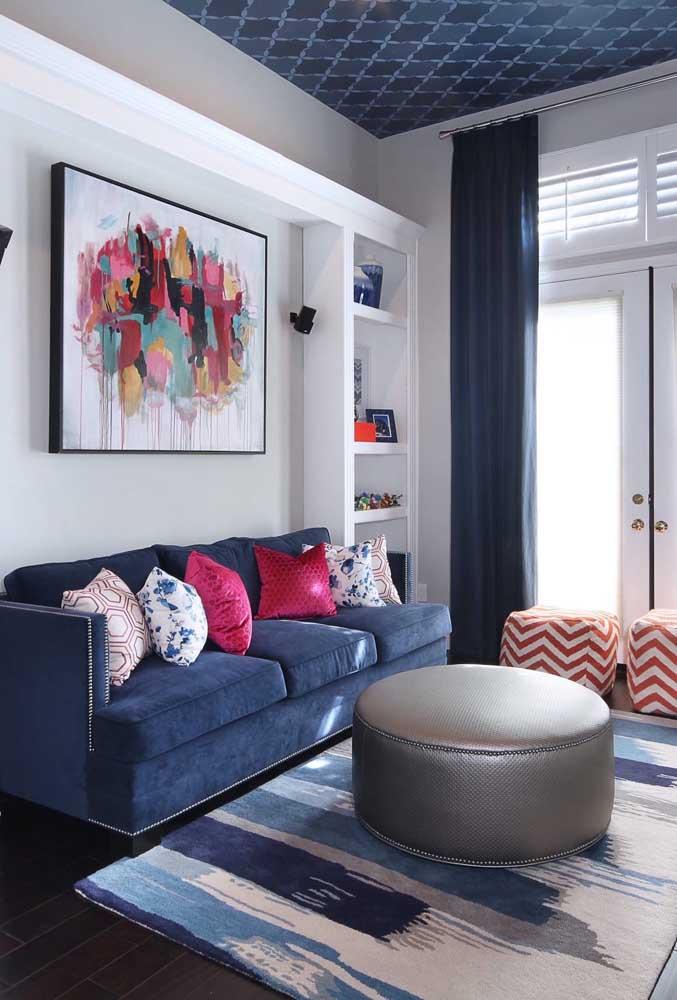 Nessa sala moderna de teto colorido, o sofá azul se harmoniza com os demais elementos no mesmo tom e forma um contraste perfeito com o vermelho