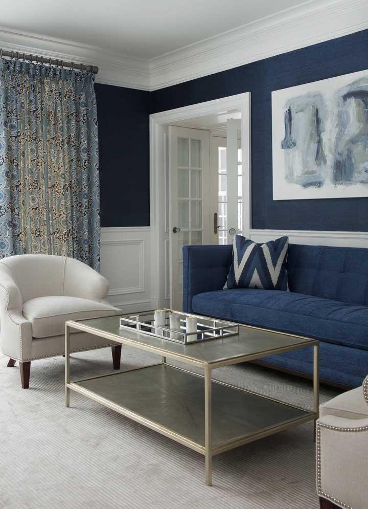 Parede e sofá compartilham o mesmo tom de azul nessa sala de estilo clássico e sóbrio