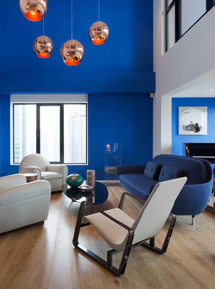 """Linda composição de tons de azul nessa sala moderna, o tom mais escuro fica no sofá; destaque para as luminárias laranja """"aquecendo"""" o ambiente"""