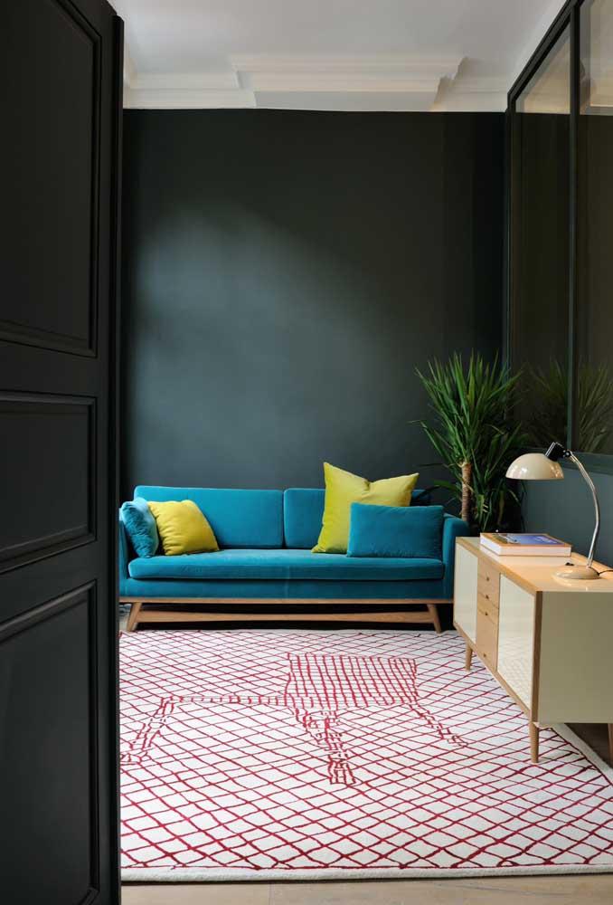 Proposta moderna de uso do sofá azul; aqui, ele vem acompanhado de almofadas amarelas e contracena super bem com o tapete de detalhes vermelhos