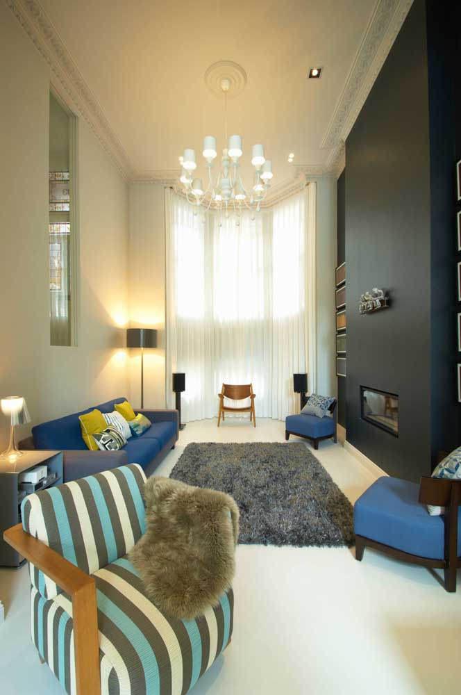 A sala de pé direito alto trouxe um sofá azul acompanhado de duas poltronas na mesma cor
