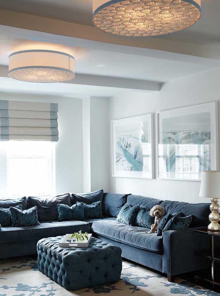 A parede branca destaca o amplo sofá azul de canto