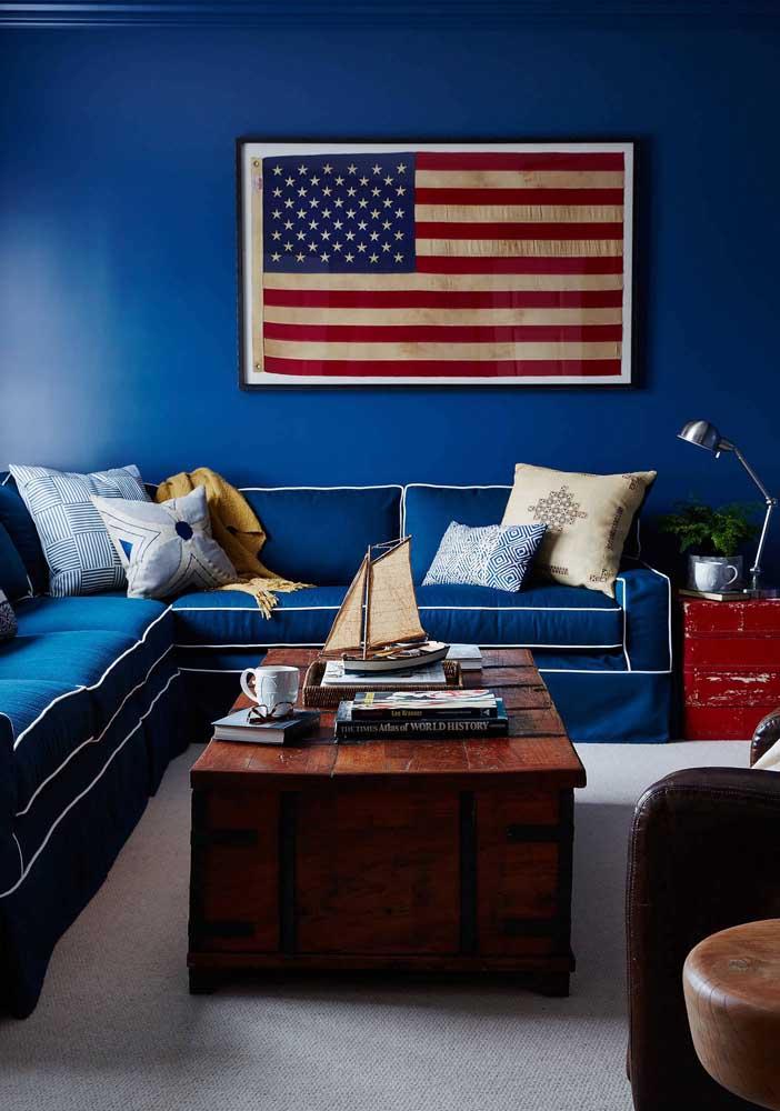 Já aqui, a bandeira norte-americana quebra a uniformidade criada pelo tom de azul que colore tanto o sofá, quanto a parede