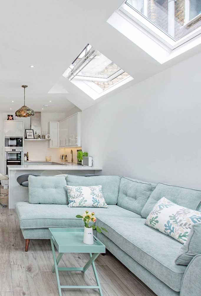 O sofá azul claro reforça a luminosidade natural que entra pelas janelas
