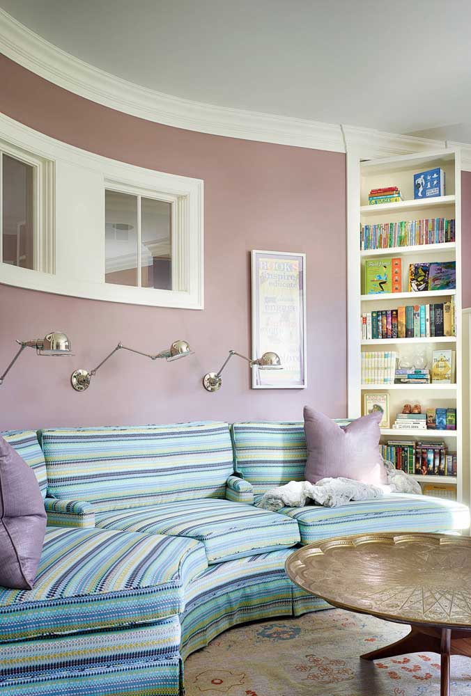 A parede rosa recebeu super bem o sofá de canto arredondado com estampa de listras azuis e verdes