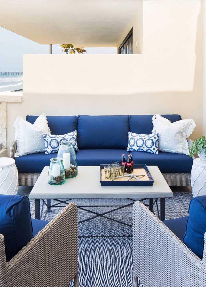 Inspiração de sofá azul que fica perfeito em uma casa de praia, graças ao detalhe de vime na base e as almofadas brancas