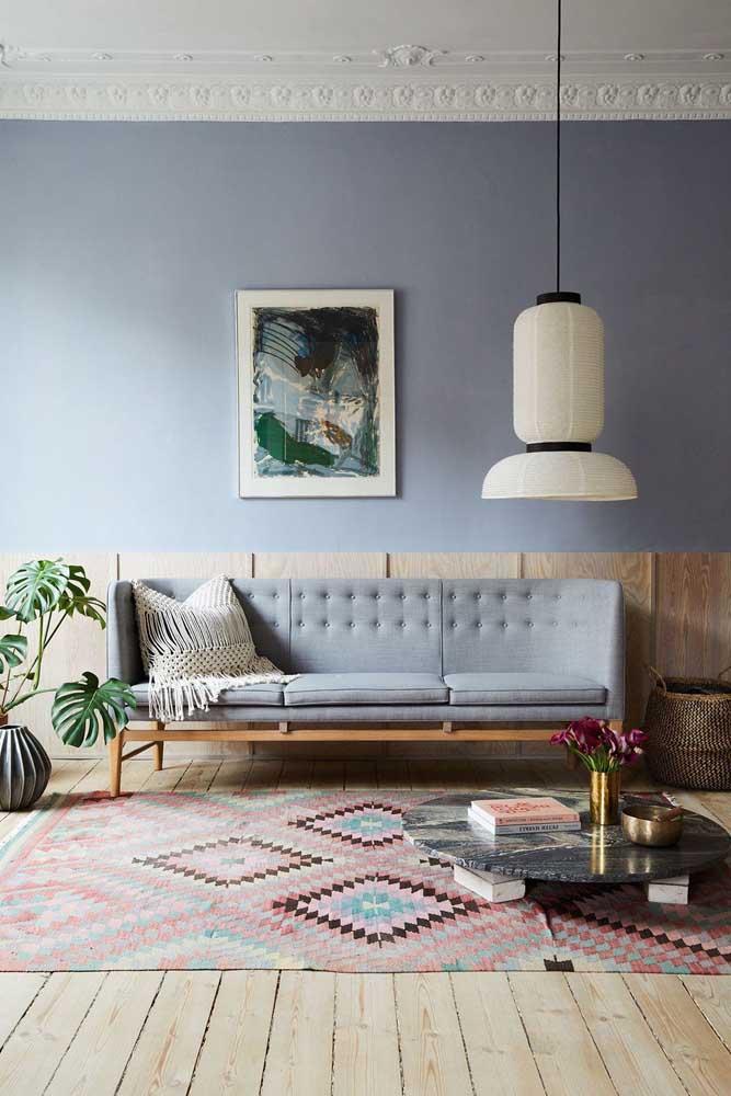 Sala de influência boho com sofá azul claro; destaque para a almofada com capa de macramê em tom cru