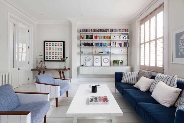 Sala ampla e neutra com sofá azul de veludo e almofadas brancas