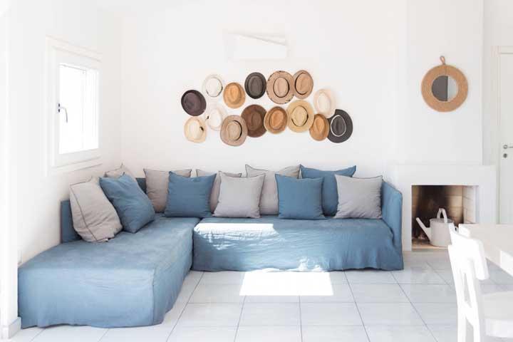 Sofá azul claro de canto recheado de almofadas para garantir o máximo de conforto