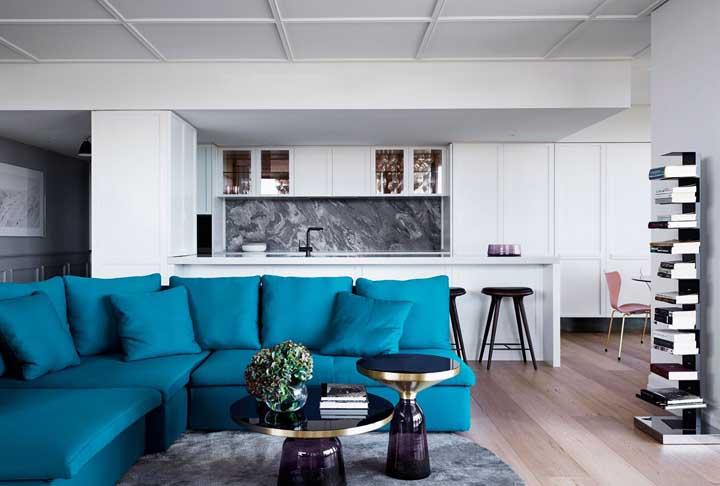 E, para fechar, um belo exemplar de sofá azul turquesa para a sala neutra em tons de branco, preto e cinza