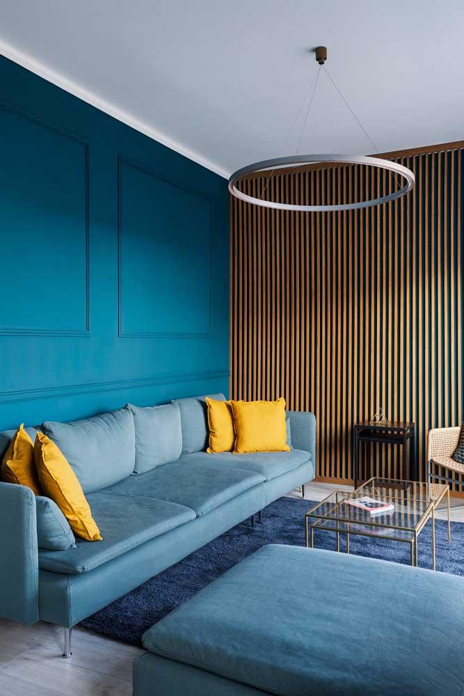 A parede com boisserie foi pintada em um tom mais escuro do que o azul do sofá, formando um conjunto que segue pelo azul do tapete