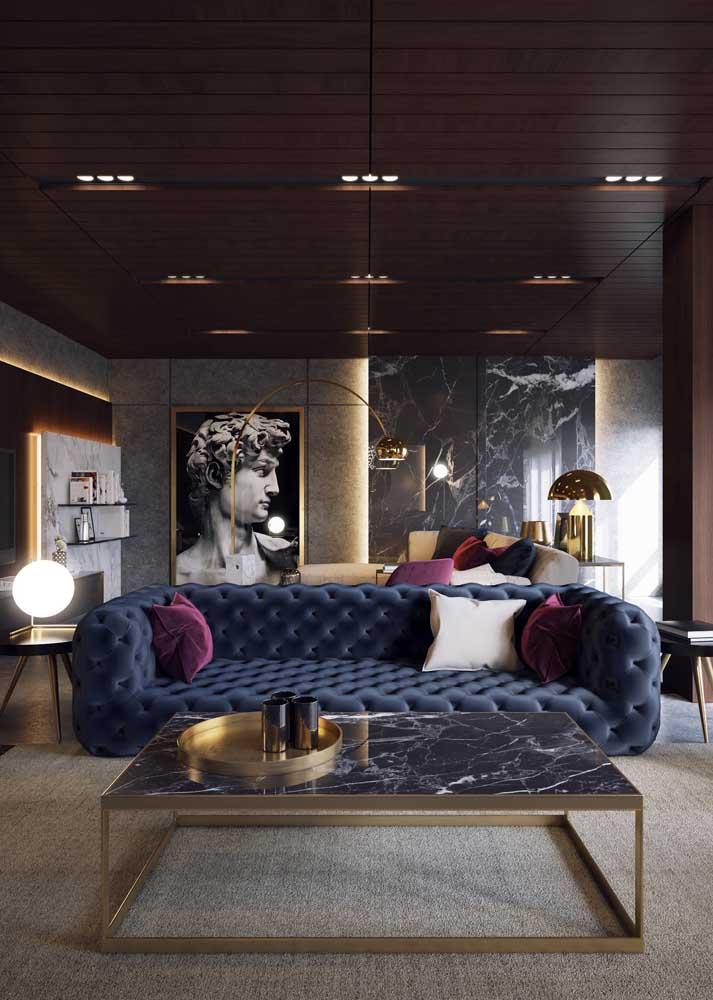 O sofá azul com acabamento capitonê traz um toque de glamour e requinte à sala de estar moderna; as almofadas roxas completam o visual