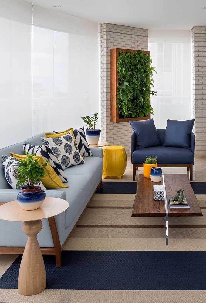 Varanda decorada com sofá azul claro e poltrona em azul petróleo; o amarelo, cor complementar ao azul, entra na decor para criar contraste