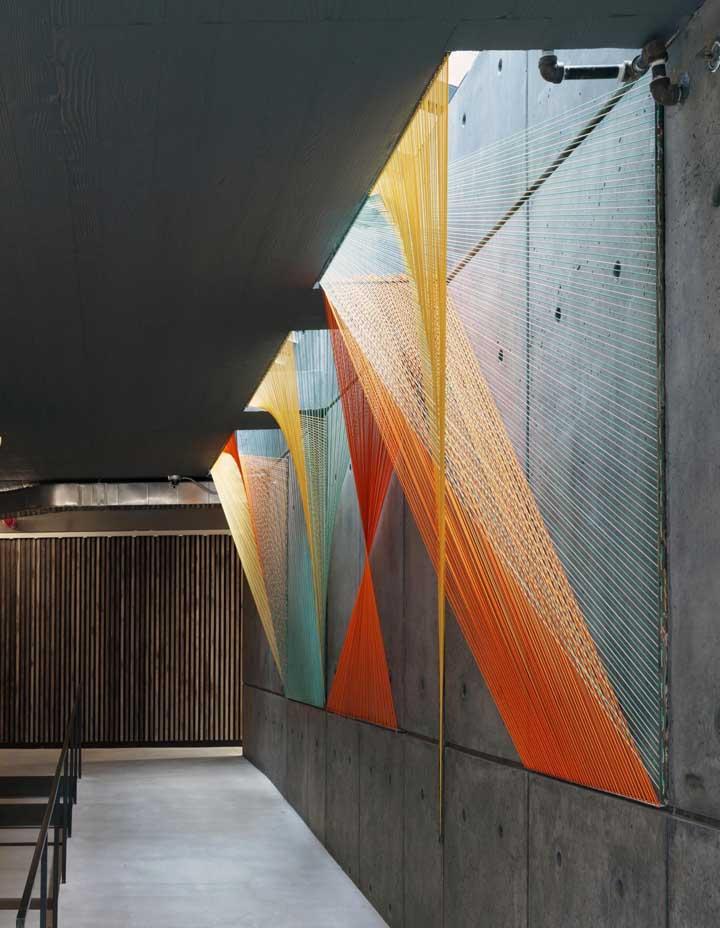 Aqui, o String Art foi além e tomou conta da parede de cimento queimado em um verdadeiro trabalho artístico, cheio de cores e estilo