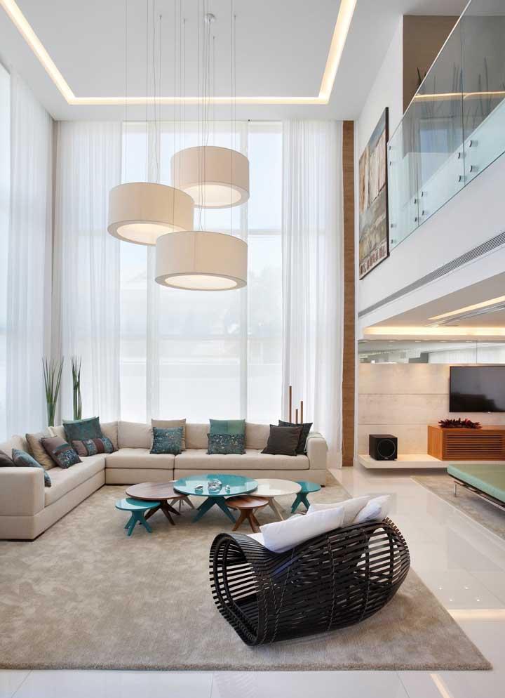 A sala de estar em pé direito duplo conta com um teto de gesso com iluminação embutida