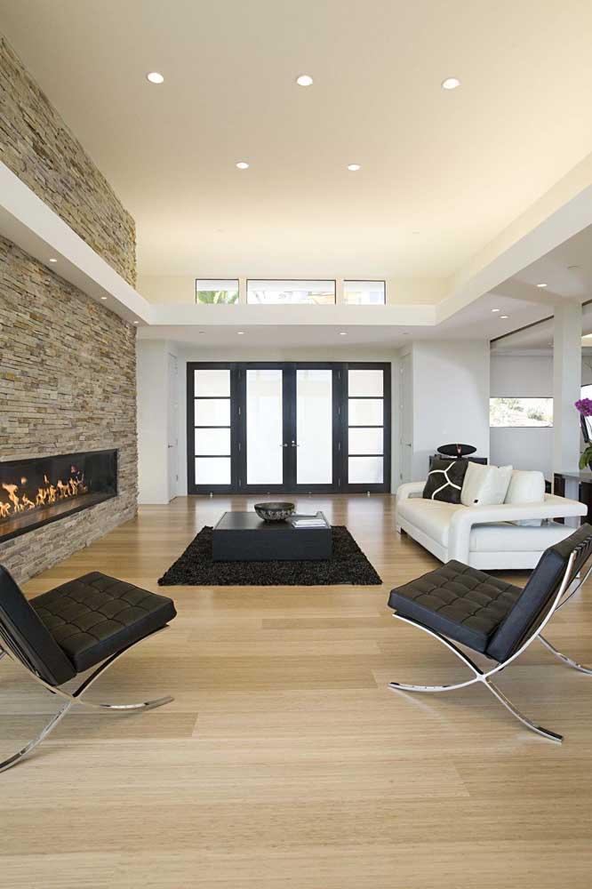 Sala de estar com pé direito duplo e teto de gesso simples com spots; repare na moldura criada com o gesso entre o primeiro piso e o mezanino