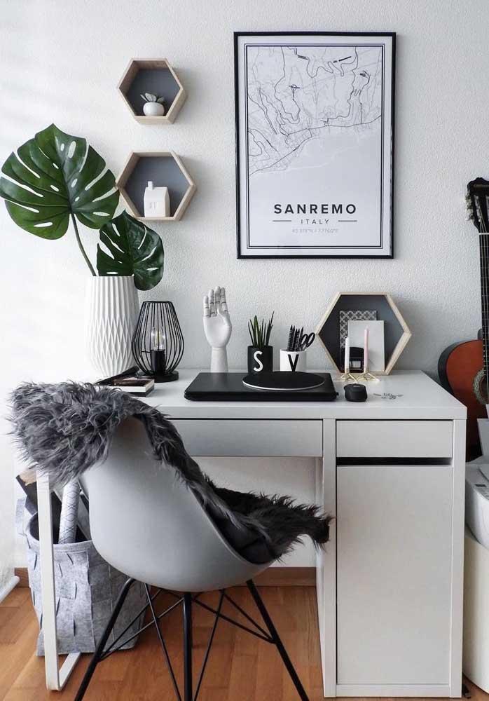 O home office clean de influência escandinava ganhou um belo vaso com folhas de Costela de Adão