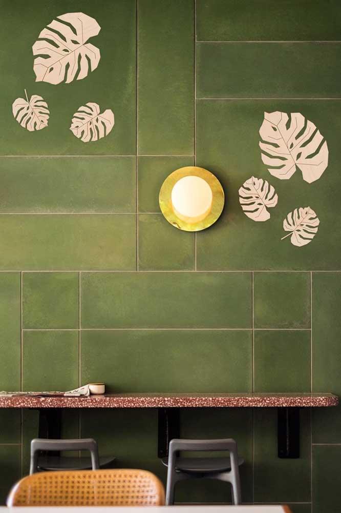 A parede verde recebeu folhas de Costela de Adão pintadas de branco, referência linda e criativa