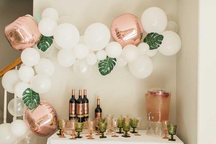Decoração de festa com arco descontruído de balões enfeitado com folhas de Costela de Adão