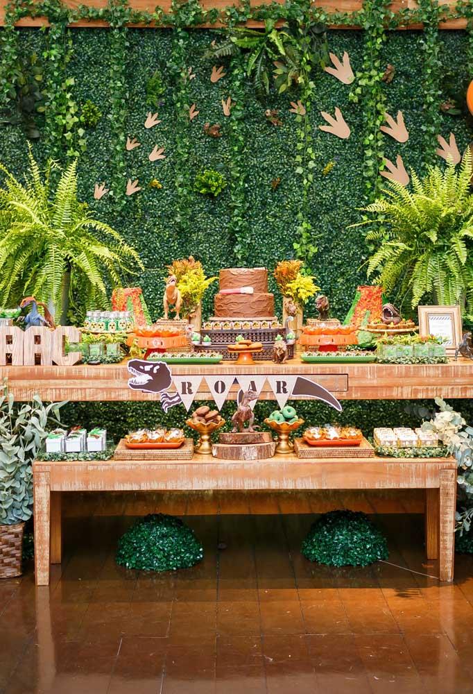 Que tal fazer um painel dinossauro como se fosse um jardim vertical? Use mesas de madeira para complementar a decoração.
