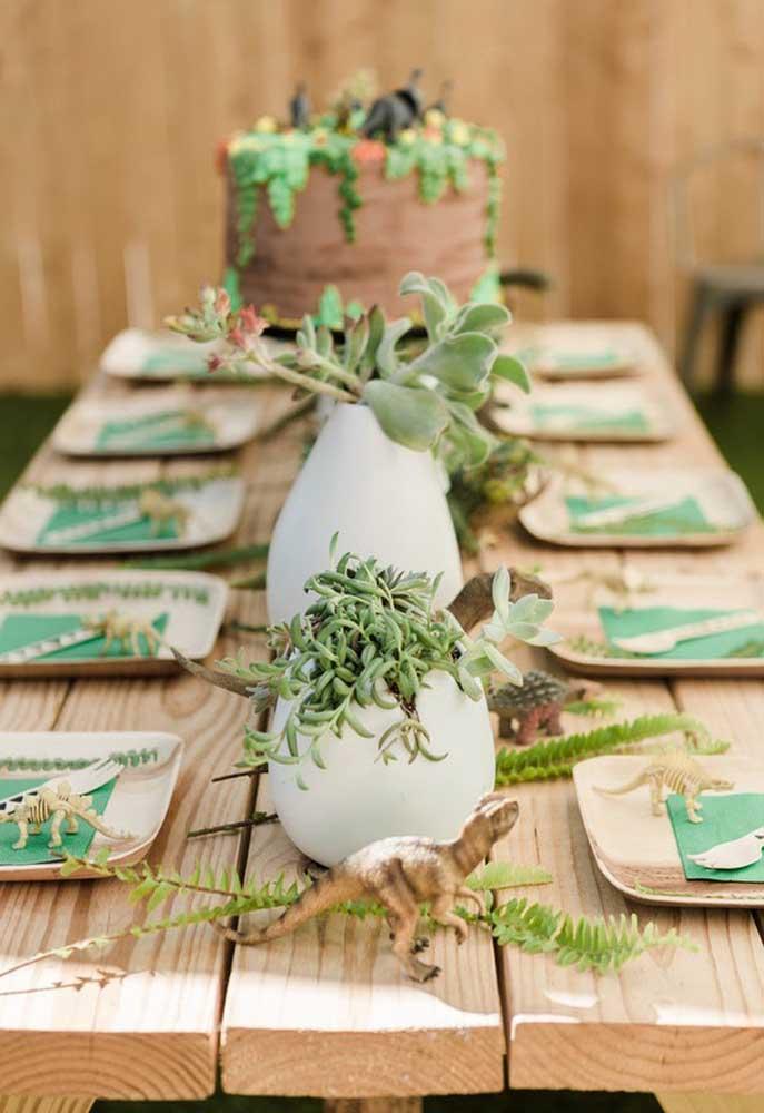 O que acha de fazer uma decoração dinossauro bem rústica? Para isso, prepare uma mesa de madeira crua e coloque vários vasos com plantas.