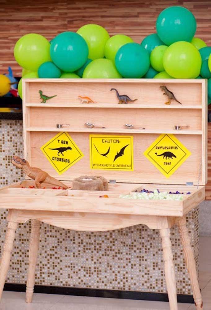Que tal fazer uma banca de madeira com vários modelos de dinossauros e outros elementos decorativos?