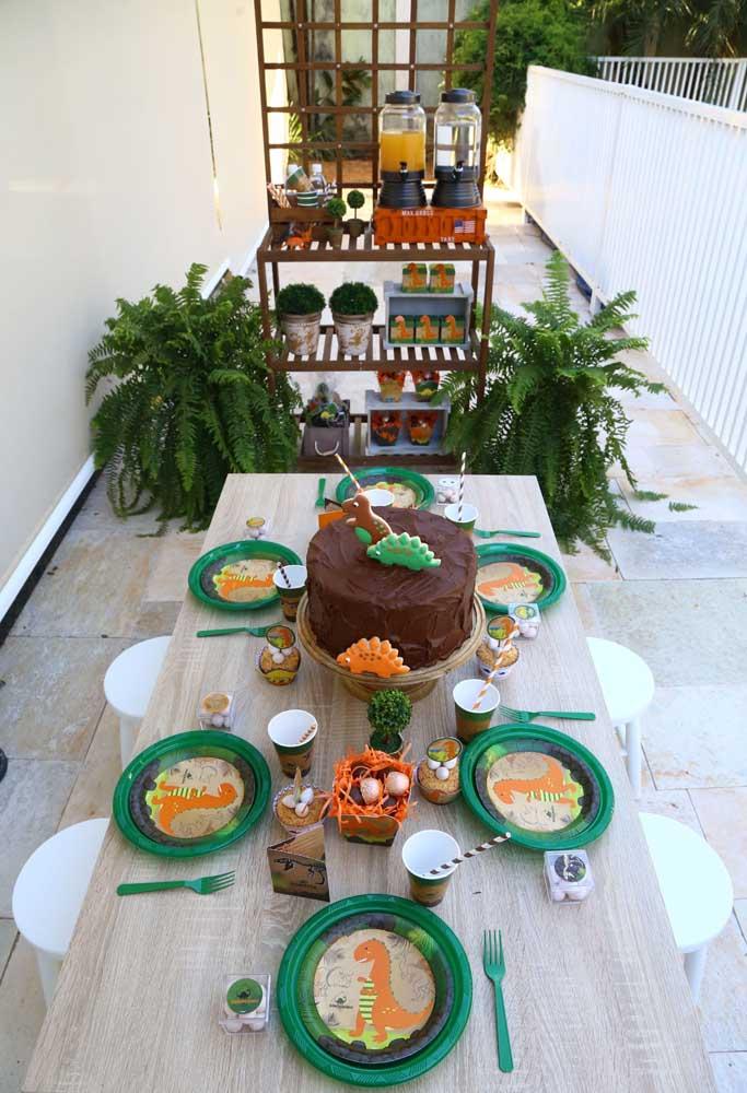 Na hora de organizar a mesa da festa, coloque os pratinhos e copos para as crianças se servirem e deixe o bolo dinossauro no centro.