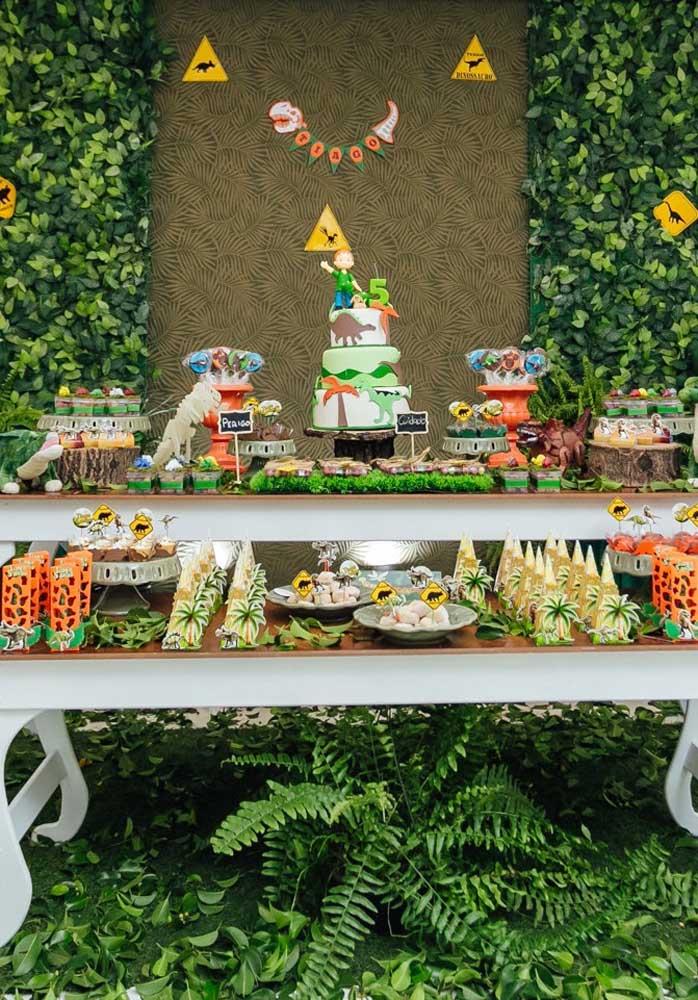 Se a intenção é fazer uma mesa de aniversário dinossauro bem farta, coloque todas as guloseimas juntas e decore com vários elementos que fazem referência ao tema dinossauro.