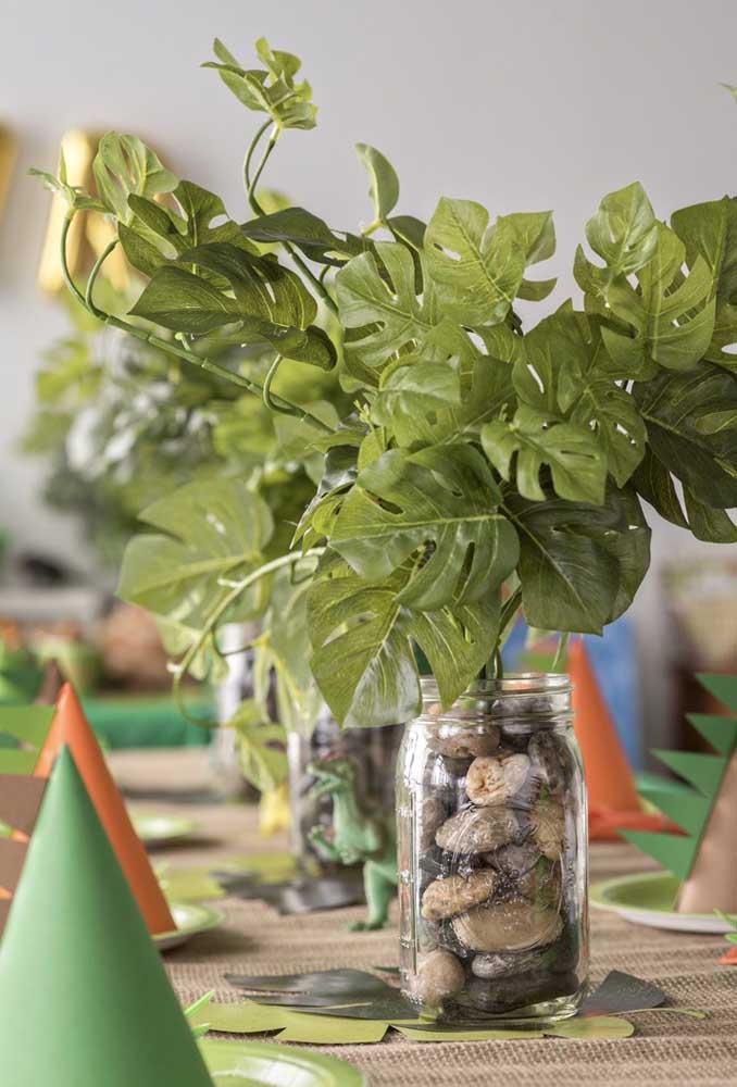 Que tal fazer um arranjo diferente para decorar a mesa? Pegue um pote de vidro, encha de pedras e coloque uma planta bem grande.