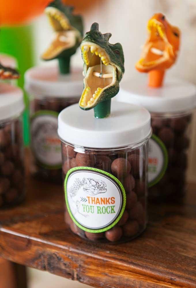 Use como lembrancinha potinhos transparentes e coloque bolinhas de chocolate. No topo decore com a cara do dinossauro.