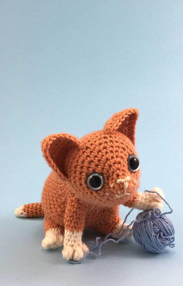 O gato é um bichinho que adora brincar com os objetos mais inusitados. Então, faça um gatinho amigurumi brincando com uma bola de linha de crochê.