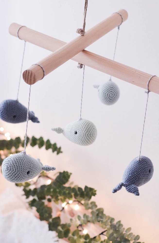 Faça várias baleias amigurumi e pendure-as em um objeto de madeira. A peça é perfeita para chamar atenção de bebês.