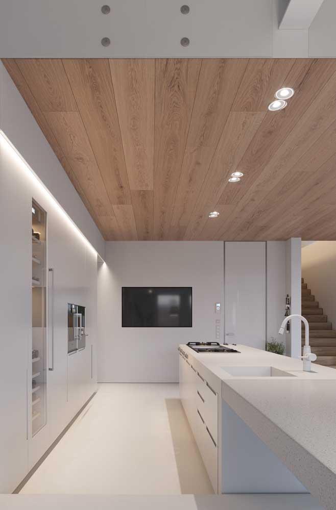 Uma cozinha branca combina perfeitamente com piso, teto e móveis amadeirados.