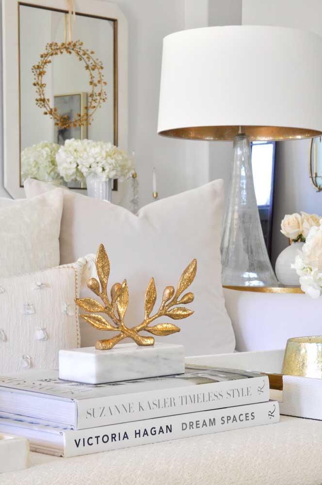 Objetos decorativos em tons dourados deixam o ambiente totalmente branco mais luxuoso.