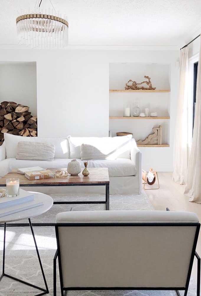 Olha que luxo essa sala branca combinando com objetos decorativos nos tons amadeirado.