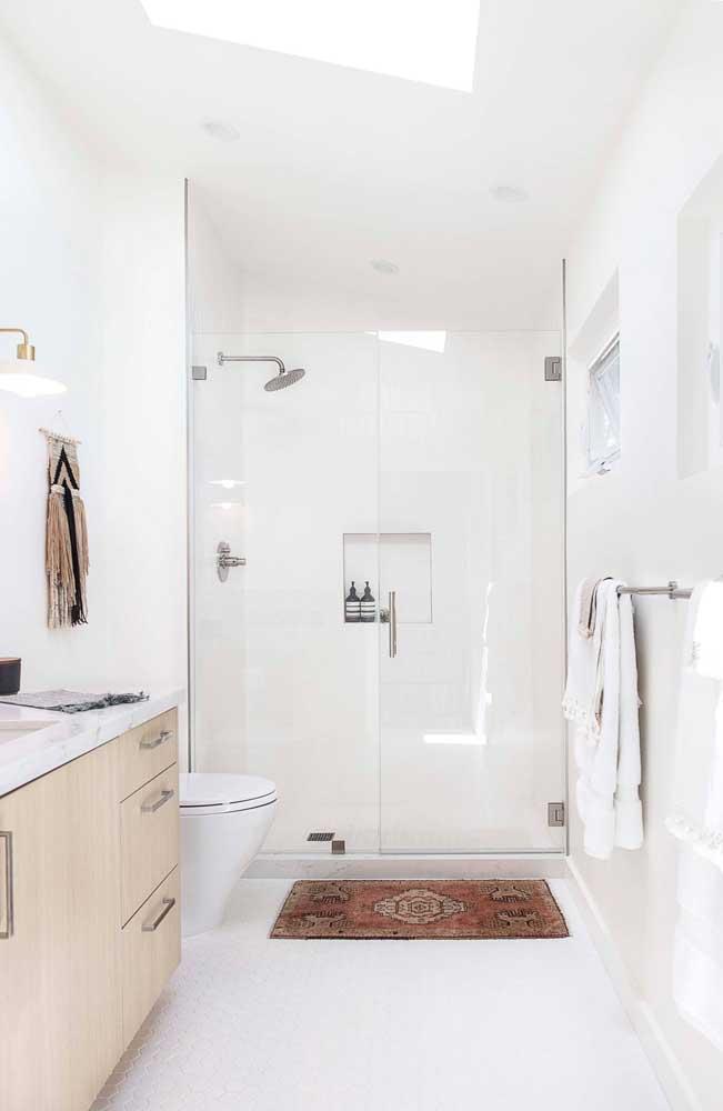 O vidro do box do banheiro com o revestimento branco na parede fazem com que o cômodo fique totalmente claro e iluminado.