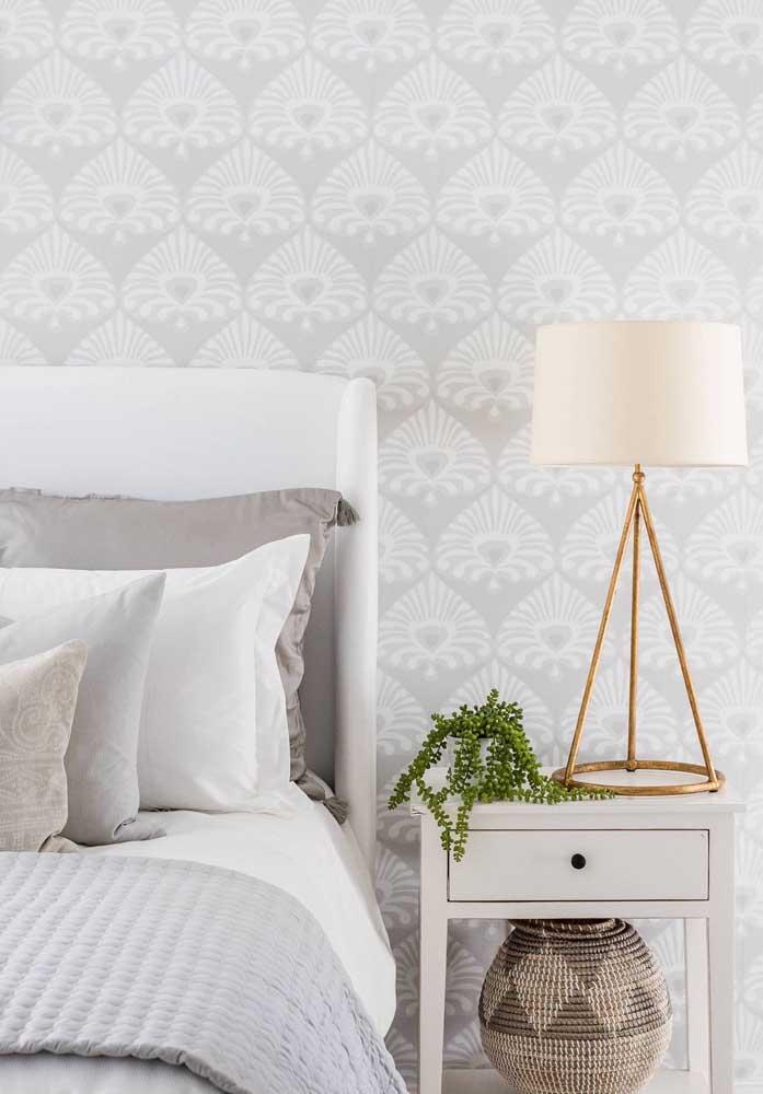 A estampa do papel de parede está combinando perfeitamente com as cores usadas no jogo de cama.