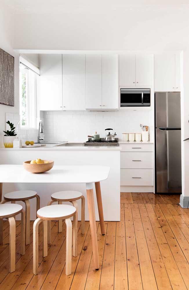 O piso de madeira dá um charme para a cozinha com parede e móveis brancos.