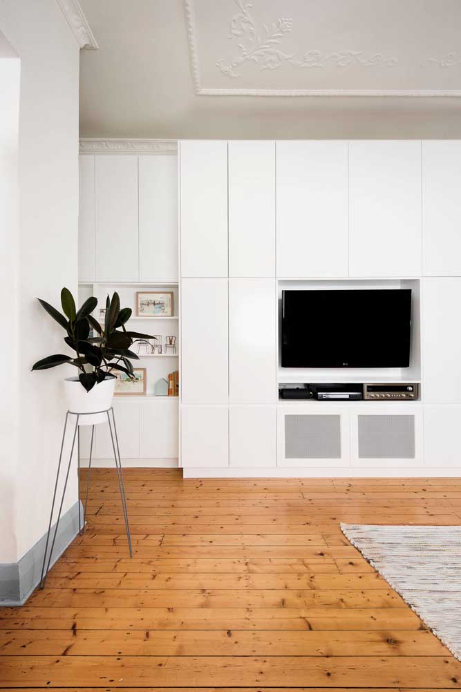 O mesmo piso também pode ser usado na sala que possui móveis, teto e paredes pintadas de branco.