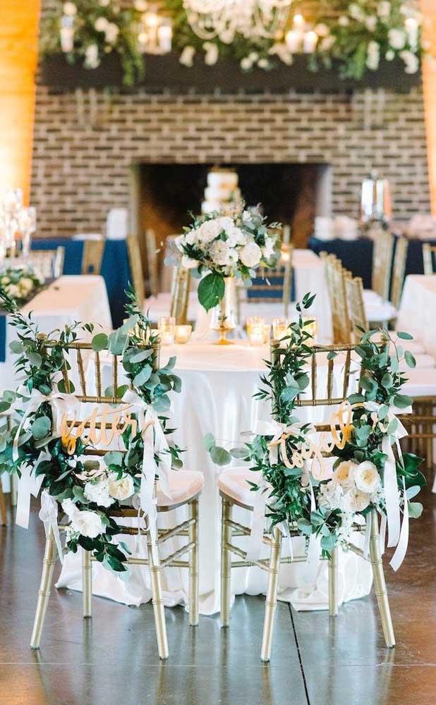 Aqui nesse casamento, as cadeiras foram decoradas com guirlandas de flores artificiais