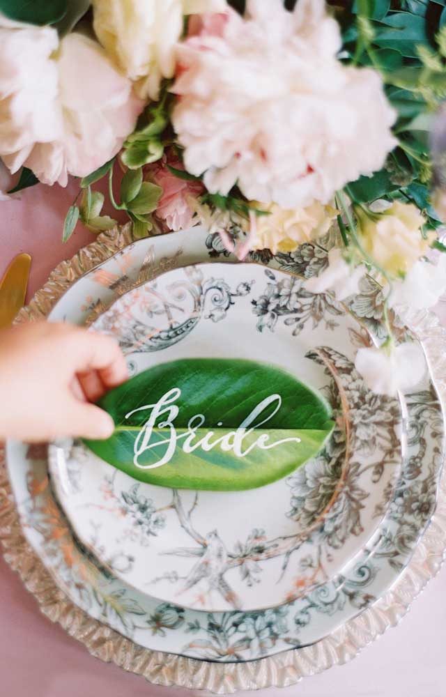 Quem diria que uma simples folha ficaria tão linda na demarcação de lugares desse casamento?