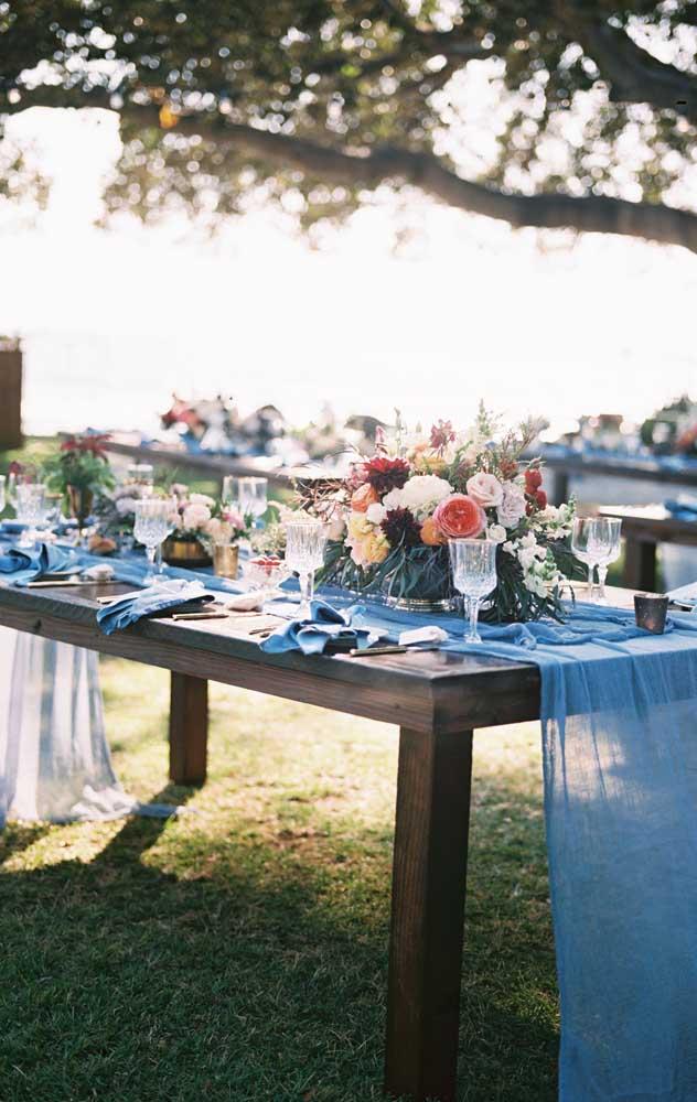 As mesas de madeira ficaram lindas com o véu azul no lugar das toalhas de mesa