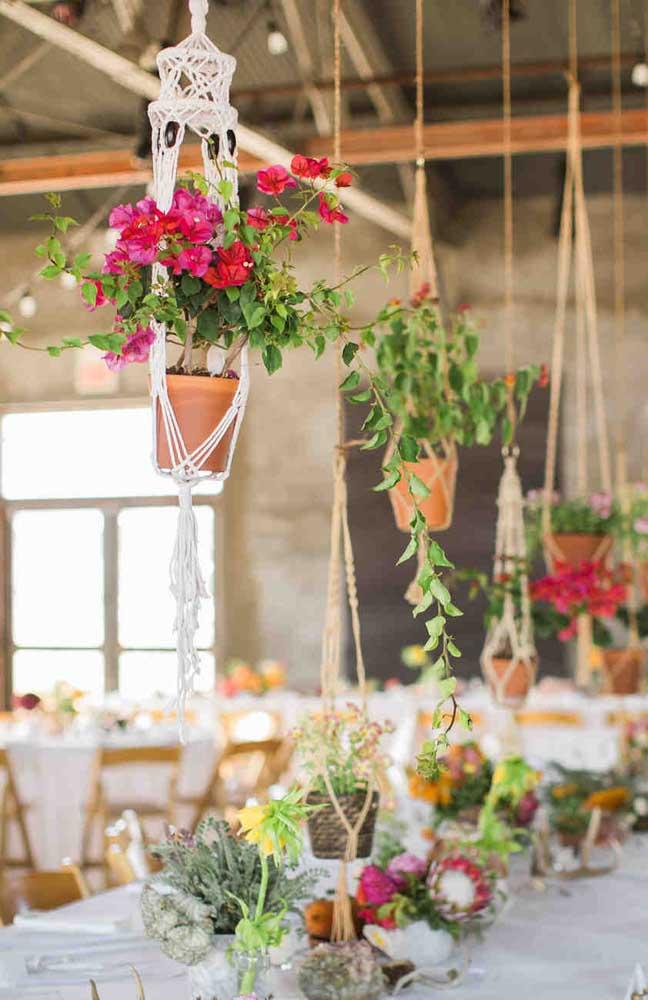 Os vasinhos suspensos ficaram super charmosos na decoração desse casamento simples e rústico