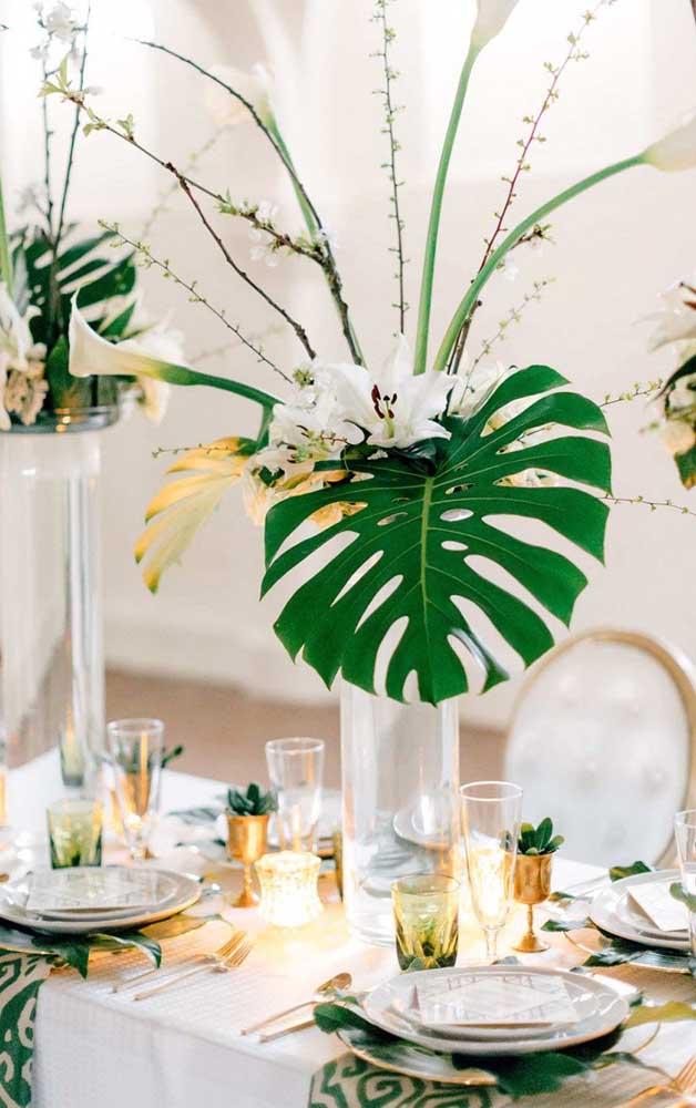 A mesa do casamento ficou encantadora com os arranjos de folhas de costela de adão