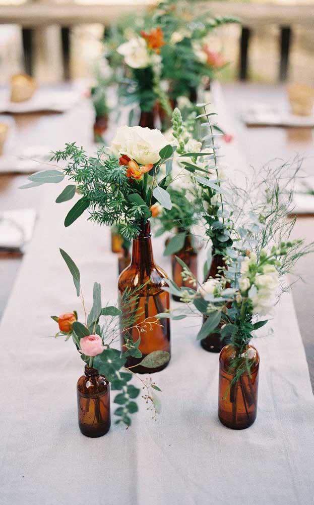 Garrafinhas de vidro reutilizadas para decorar a mesa do casamento simples