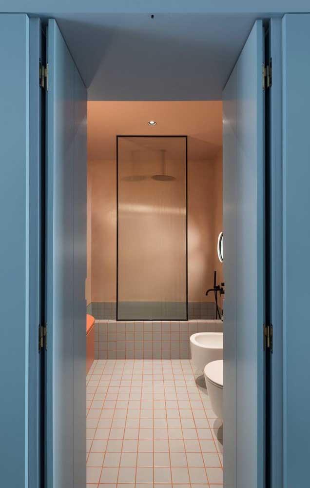 As paredes e portas azuis dessa casa escondem um banheiro cor de rosa muito charmoso; um belo contraste