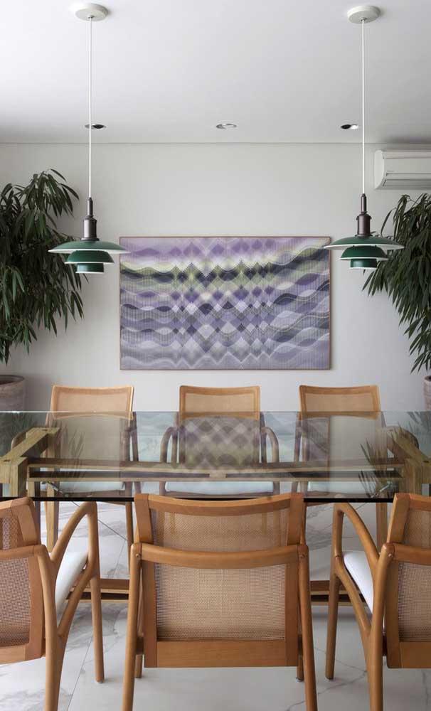 Essa sala de jantar de estilo contemporâneo apostou em detalhes significativos para completar a decoração, como as luminárias e o quadro
