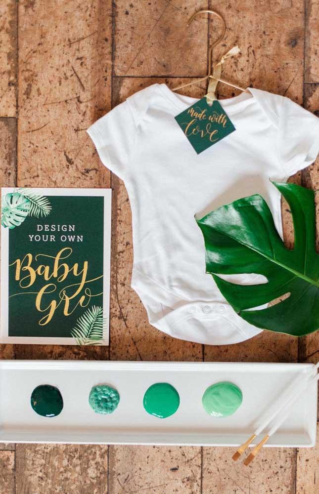 Uma camisetinha, tintas e pincel para os convidados do chá de bebê estamparem um desenho ou uma mensagem