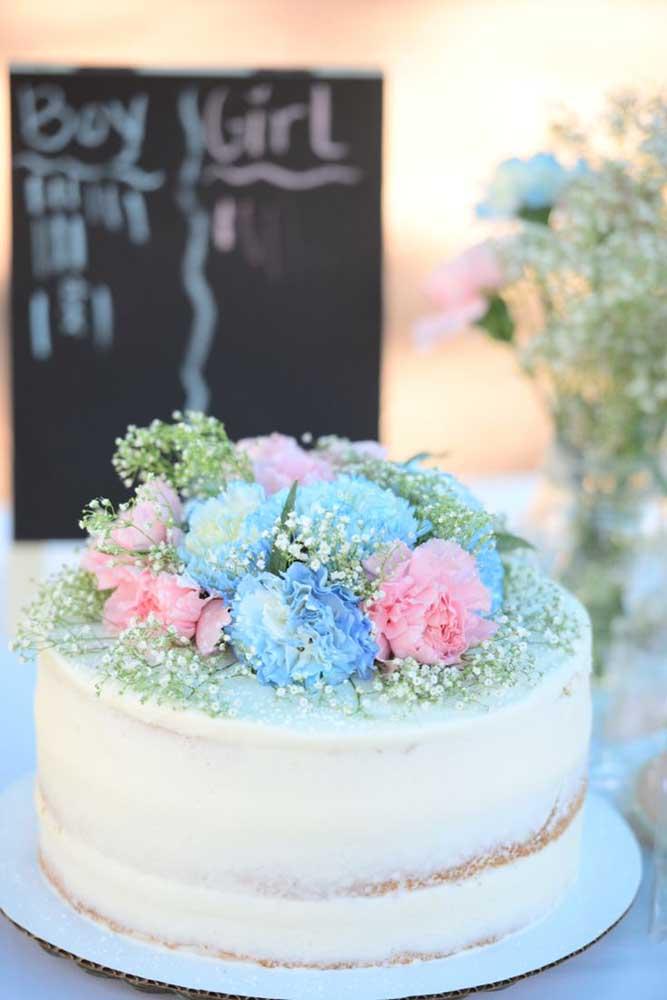 Bolo com flores rosas e azuis para o chá revelação