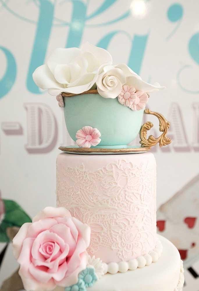 O bolo segue o estilo de renda e no topo foi colocada uma xícara com flores.